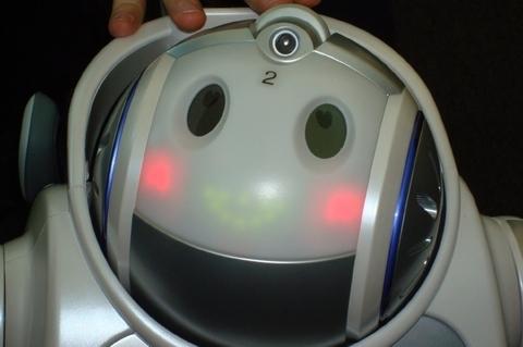 """Розовощекий iRobi Q с очаровательной желтой улыбкой и горящими сердечками в глазах создан для того, чтобы люди не испытывали неудобств в """"общении"""" с ним. Microsoft использует его в качестве прототипа для разработки программного обеспечения, которое сделает его еще более полезным. Трауэр говорит, что такой или похожие не него роботы могут появиться в домах в ближайшие три - пять лет."""
