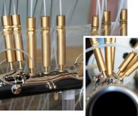 Робот вцелом состоит из двух частей. Есть часть сманипуляторами, которые управляют клапанами,— это все медные трубки. Аза ними видна такая штука, набитая чем-то белым,— так вот это камера воздушного давления, вкоторую помещен мундштук кларнета. Она действует как рот музыканта