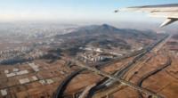 Вид на Сеул и пригороды с самолёта — картина, характерная для всей страны. Любой плоский участок земли либо застроен, либо используется для нужд сельского хозяйства