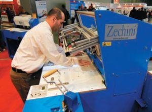 Крышкоделательная машина Zechini Roby Junior II: оператор выставляет каблук устройства для автоматического обжима уголка крышки. Нечастая опция на подобных машинах