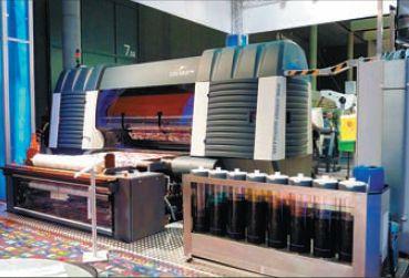 Даже на фоне огромных 5-метровых сверхширокоформатных принтеров Zimmer Colaris 1800 для печати по тканям кажется настоящим монстром — только посмотрите на эти ёмкости для чернил!