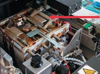 В КБC Heidelberg Eurobind600 опциональный третий валик (указан стрелкой) подогревается— для этого служит видимый справа от него красный провод. Валик имеет обратное вращение и разглаживает клей на корешке более ровным слоем, что позволяет бороться с пропусками клеевого слоя на широких корешках. Опция рекомендуется при работе с толстыми блоками