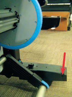 Стрелкой показан оптический датчик устройства намотки, благодаря которому материал всё время поддерживается в натянутом состоянии. Слева вверху видна металлическая ось для намотки материала: благодаря рёбрам жёсткости она обладает лёгкостью и прочностью